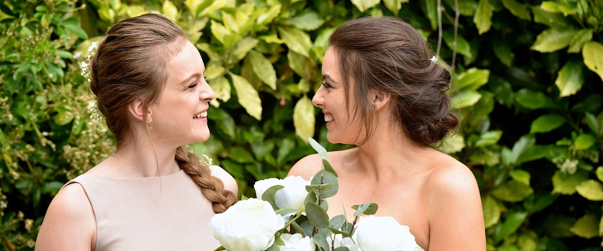 Bride and Bridesmaid smiling at each other